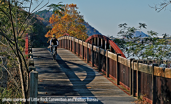 Wooden bridge over Jimerson creek, by the Arkansas River with biker